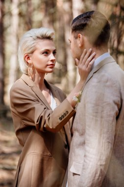 Selective focus of stylish woman touching man face stock vector
