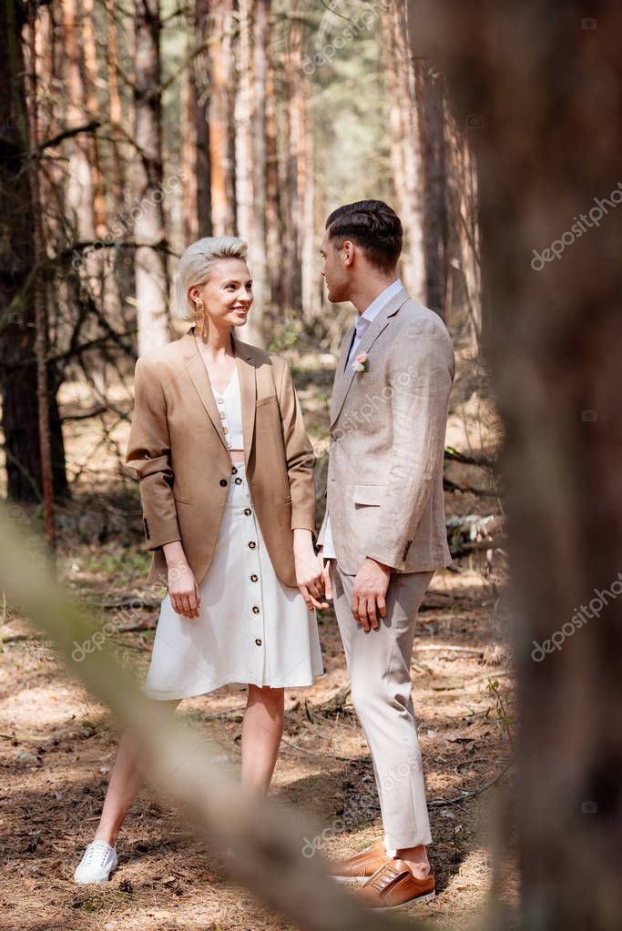 Selective focus of handsome man and attractive woman holding hands in forest stock vector