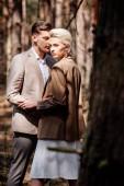 Stylová blondýnka objímající manžela v lese