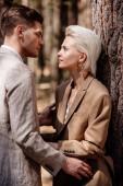 Stylový pár ve formálním oblečení, který se dívá jeden na druhého v lese