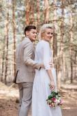 smiling bridegroom in formal wear embracing bride in forest