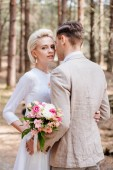 just married couple in formal wear embracing in forest