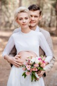 smiling married couple with wedding bouquet embracing in forest