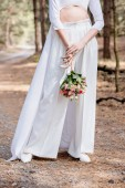 cropped view of bride in white attire holding wedding bouquet in forest