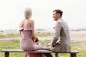 nevěsta s kyticí a ženichem sedícího na lavici