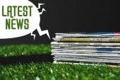 Fotografia stack of different print newspapers on fresh green grass near speech bubble with green latest news lettering isolated on black