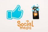 Fotografie blauer Daumen nach oben Zeichen in der Nähe von Smartphone mit Social-Media-Symbole auf weiß isoliert