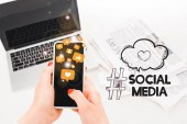 selektivní zaměření ženy přidržením telefonu Smartphone se sociálními ikonami v blízkosti notebooku a novin