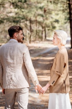 stylish smiling couple holding hands and looking at each other in forest