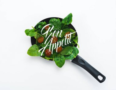 fresh spinach leaves and cherry tomatoes in frying pan with bon appetit lettering on white background