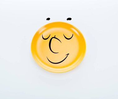 Top view of shiny yellow plate with pleased smiley on white background stock vector