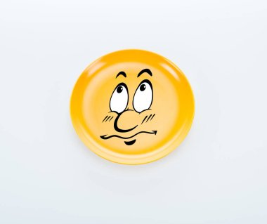 top view of shiny yellow plate with sad smiley on white background