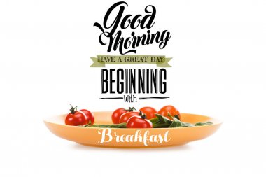 cherry tomatoes with green spinach leaves in yellow plate with good morning, have a great day beginning with breakfast lettering above isolated on white
