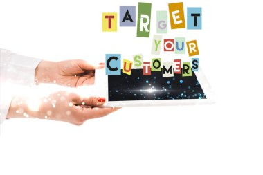Cropped view of woman holding digital tablet with target your customers lettering isolated on white stock vector