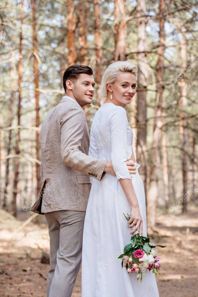 Smiling bridegroom in formal wear embracing bride in forest stock vector
