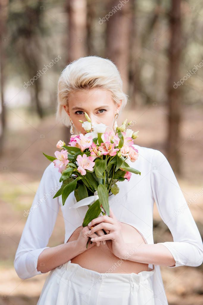 Attractive blonde bride holding wedding bouquet in forest stock vector