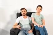 figlio e padre con telecomando guardando la tv in salotto