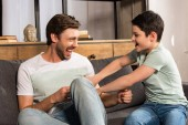laughing son and dad sitting on sofa and having fun in living room
