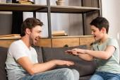 Smějící se syn a táta sedí na pohovce a baví se v obývacím pokoji