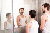 usměvavý syn a táta se dívali na zrcadlo v koupelně
