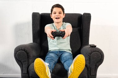 KYIV, UKRAINE - APRIL 17, 2019: excited boy with joystick sitting in armchair and playing video game stock vector