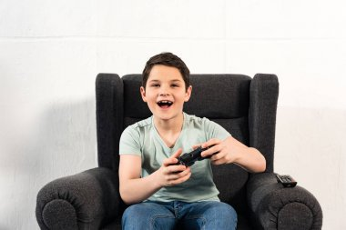 KYIV, UKRAINE - APRIL 17, 2019: excited boy with joystick sitting in armchair and playing video game