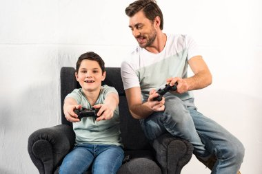 KYIV, UKRAINE - APRIL 17, 2019: smiling son and dad holding joysticks and playing video games together stock vector