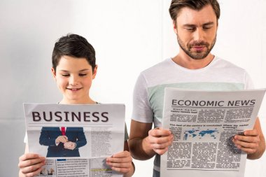 smiling son and concentrated father reading newspapers at home