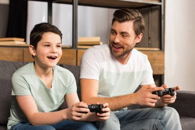 KYIV, UKRAINE - APRIL 17, 2019: smiling father and son holding gamepads and playing video games in living room stock vector