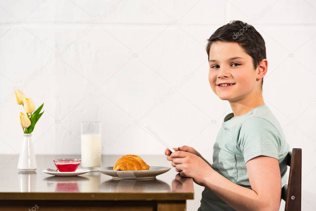 Smiling boy using digital tablet during breakfast in kitchen stock vector