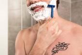 oříznutý pohled muže s úsměvem na holení plnovous s břitvou v koupelně