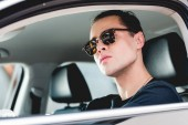 selektivní zaměření pohledného stylového muže na sluneční brýle v autě