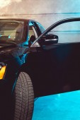 black shiny luxury car with open door in garage with smoke