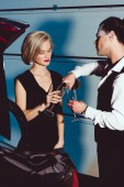stylish man and young woman with champagne glasses near car