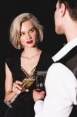 man pouring champagne for beautiful fashionable young woman