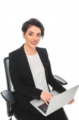 smiling mixed race businesswoman using laptop while sitting in office chair and looking at camera isolated on white