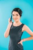 usmívající se smíšená závodní žena mluvící na telefonu Smartphone a držící ruku na hip izolovanou na modré