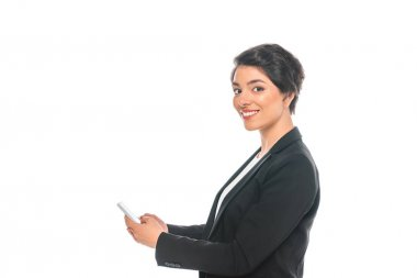 cheerful mixed race businesswoman using smartphone while smiling at camera isolated on white