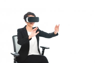 young mixed race businesswoman gesturing while sitting in office chair and using virtual reality headset isolated on white