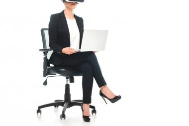 Partial view of mixed race businesswoman using virtual reality headset while sitting in office chair and using laptop on white background stock vector