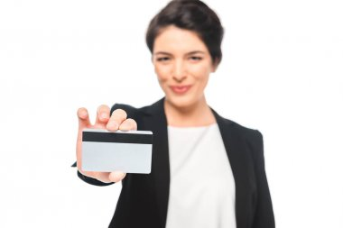 Selective focus of smiling mixed race businesswoman showing credit card isolated on white stock vector