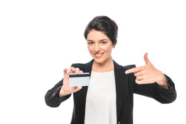 cheerful mixed race businesswoman pointing with finger at credit card and looking at camera isolated on white