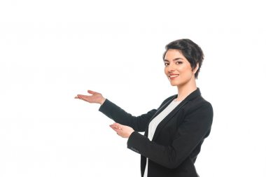 attractive mixed race businesswoman gesturing and smiling at camera isolated on white