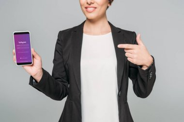 KYIV, UKRAINE - APRIL 24, 2019: Partial view of mixed race businesswoman pointing with finger at smartphone with Instagram app on screen isolated on grey. stock vector