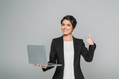 beautiful mixed race businesswoman holding laptop and showing thumb up isolated on grey