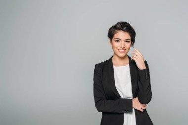 cheerful mixed race businesswoman in black formal wear smiling at camera isolated on grey