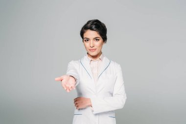 attractive mixed race doctor looking at camera with raised hand isolated on grey