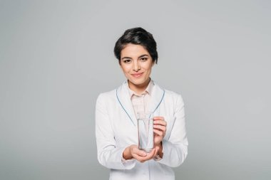 Pretty mixed race doctor holding glass of water while looking at camera isolated on grey stock vector