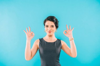 cheerful mixed race woman showing ok gesture while smiling at camera isolated on blue
