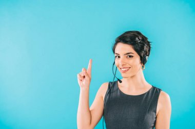 Cheerful mixed race call center operator in headset showing idea sign isolated on blue stock vector